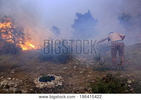 Zrnovnica, Split, Croatia - July 17, 2017: Man fighting with the massive wildfire burning down the forest and villages around city Split