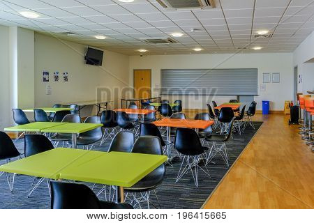 Essex England UK -June 12 2017:Empty canteen with tables and chairs and serving hatch. Light and airy room.