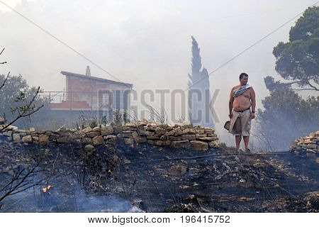 Zrnovnica Split Croatia - July 17 2017: Man standing on the rubble after defending of the massive wildfire burning down the forest and villages around city Split