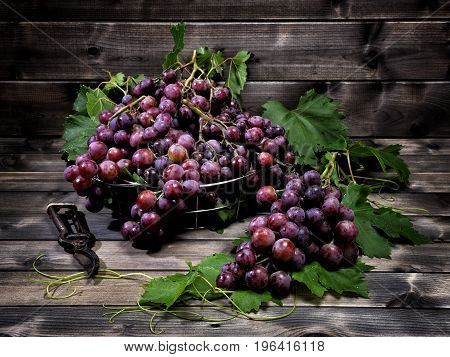 Fresh red grapes bunch lying on leaves on an old wooden table.