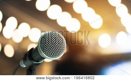 Microphone on abstract blurred of speech in seminar room or speaking conference hall light Event concert bokeh background