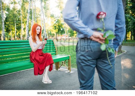 Man gives woman flower, romantic date