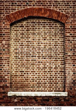 Old bricked-up window with arch. Architectural feature in red brick with white stone windowsill. Decorative frame with space for text