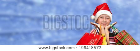 Little Girl In Fur-cap With Shopping Bags On Blue Background. Christmas