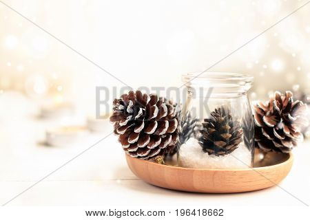 Beautiful winter home decor background. Pine cones in glass jar and candles, copy space. Dreamy light and soft focus, bokeh effect.