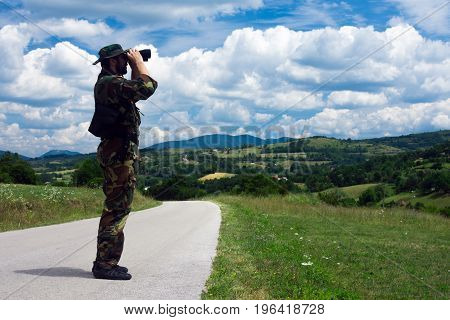 The soldier in uniform from military is looking away with binoculars in nature.