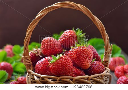 Fresh strawberries in the wicker basket on wooden table close up