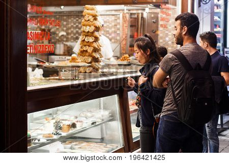 Turkey Istanbul June 2017 the company of young people choose sweets at the window with baklava , a girl of Asian appearance surprised