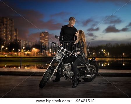 A guy a girl and a motorcycle. The side of the road the lights of the night city