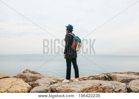 Girl traveler in a hat with a backpack next to the sea. Travel, hiking.
