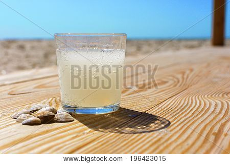 A glass of soda lemon water on the wooden boards on the beach.