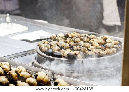 Turkish roasted chestnuts on a mobile street stall , steam.