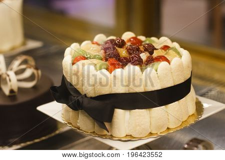 Colorful mixed fruit fresh cream cake in refrigerator showcase.
