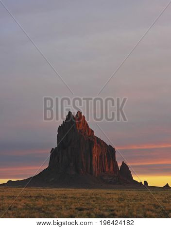 A Glowing Shiprock Landscape Against a Striated Sunrise Sky New Mexico on the Navajo Reservation west of the town of Shiprock.