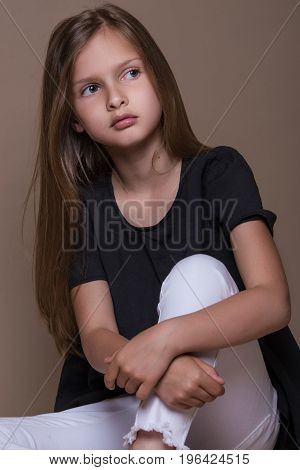 Portrait Of Cute Little Girl With Dark Hair In Studio Over Beige Background.