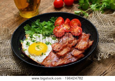 Fried egg with bacon tomatoes and parsley in frying panclose up