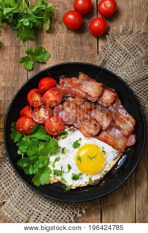 Fried egg with bacon tomatoes and parsley in frying pan top view