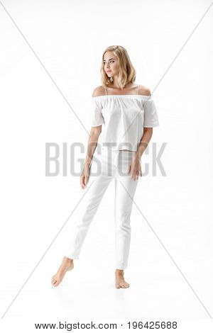 Beautiful smiling blond woman in a white blouse and pants on a white background