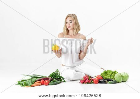 Beautiful blond woman in white clothes and lots of fresh vegetables on a white background. Girl holds bell pepper