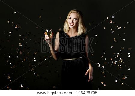 Beautiful happy blonde woman holding a glass of white wine on a black background with confetti