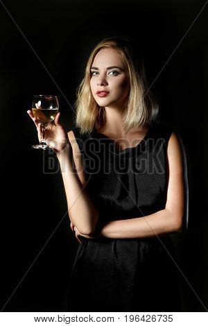 Beautiful blonde woman with a glass of white wine on a black background
