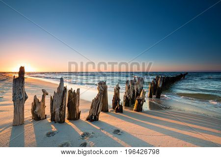 Sunset on the Baltic Sea beach and old wooden breakwater