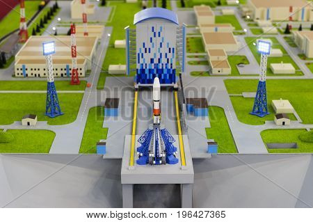 Spaceport scale model with spaceship on launch platform, layout of rocket ready to start with floodlights, buildings and roads on blurred background, aerospace industry, selective focus