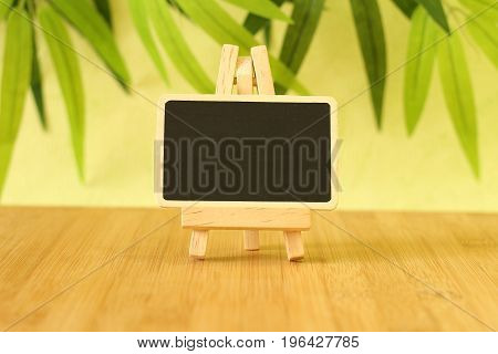 Small empty slate in width to write a message that is posed on an easel all on wooden floor and green foliage background