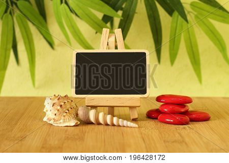 Small empty slate in width to write a message posed on an easel on a wooden floor with red pebble and beach shells on a green foliage background