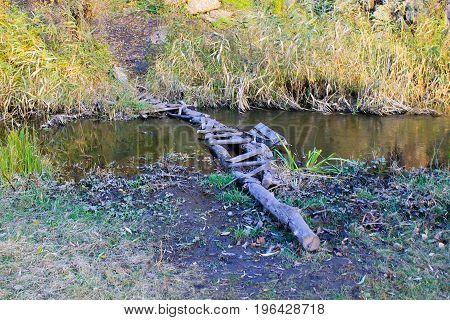 Narrow old wooden bridge across small river