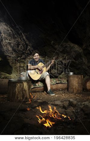 Man relaxing in wilderness with guitar and eating hunted fish