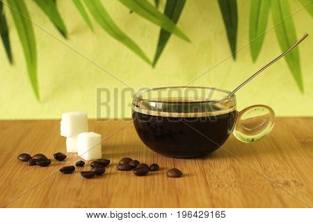 A cup of black coffee on a brown bamboo wood floor with pieces of sugar stacked next to it and coffee beans on a green foliage background