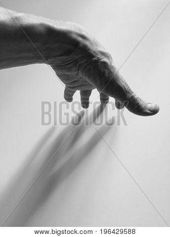 Black and white photo of male hand casting shadow on the wall.