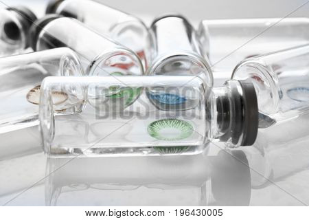 Bottles with contact lenses on white background