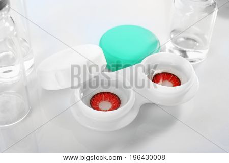 Container with contact lenses on white background