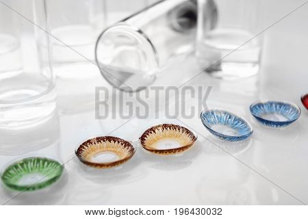 Contact lenses and bottles on white background