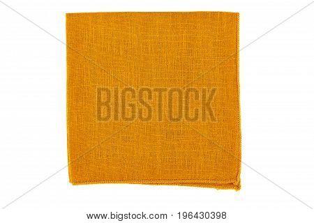 Folded orange textile napkin isolated on white background