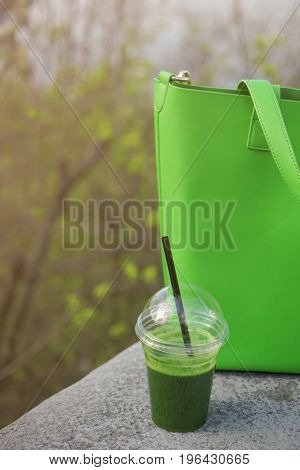 Cup of fresh vegetable smoothie and  green bag on street
