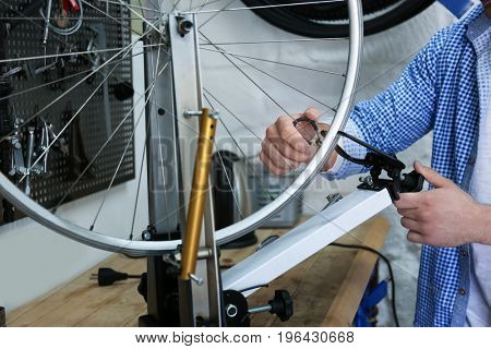 Young man working in bicycle repair shop