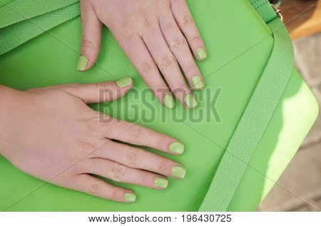 Beautiful female hands with green manicure on bag