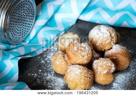 Homemade small donuts with powdered sugar on brown marble background