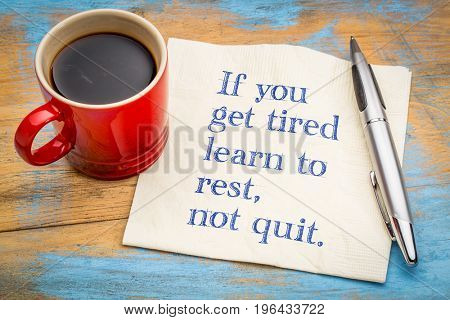 If you get tired learn to rest, not quit - inspirational handwriting on a napkin with a cup of coffee