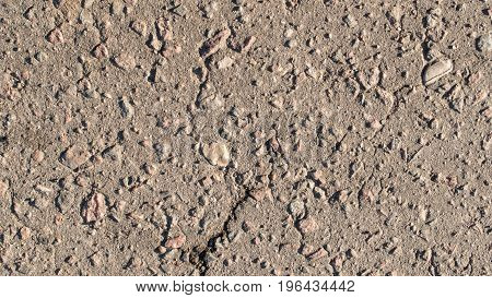 The texture of asphalt with large stones.