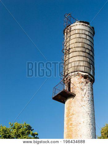 rusted industrial water tower against blue skies
