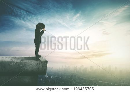Young Afro businessman standing on the top of a skyscraper while using binocular for looking an opportunity