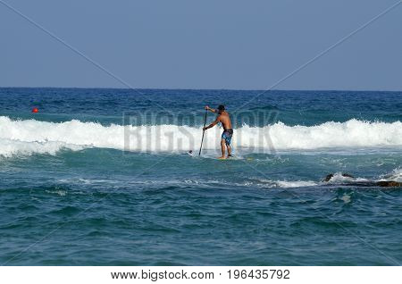 Stand Up Paddling Surfing with a paddle in the sea on the waves
