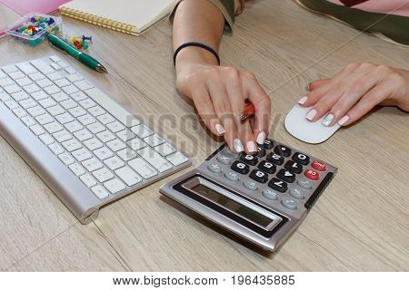 Young woman working in office sitting at desk using computer. Business executive woman at workplace. Businesswoman Calculating Tax At Desk In Office