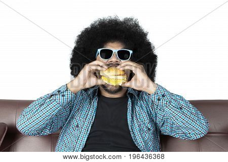Portrait of afro man eating yummy hamburger while sitting on the brown couch in studio