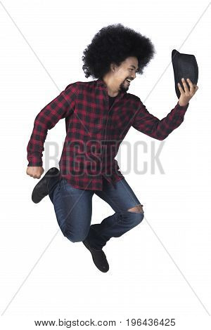 Portrait of Afro man jumping high and holding his hat on white background
