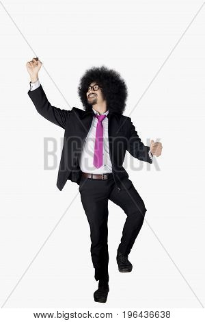 Full length of Afro businessman with curly hair using a marker to write on whiteboard. Isolated on white background